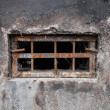 Small dark basement window with rusted steel lattice — Stock Photo