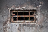 Small dark basement window with rusted steel lattice — Stock Photo