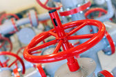 Macro photo of red industrial valve on gray pipelines — Stock Photo