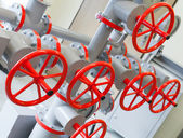 Group of red industrial valves on gray pipelines system — Stock Photo