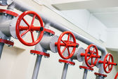 Red industrial valves in a row on gray pipelines system — Stock Photo