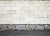 Urban background texture with stone wall and asphalt ground — Stock Photo