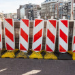 Red and white striped warning road signs stand on the border of street area under construction in historical center of Amsterdam — Stock Photo