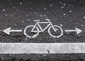 Bicycle lane. White road marking with arrows on dark asphalt — Stock Photo