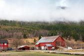 сельских норвежский пейзаж с красной деревянных домов и облака на холмах — Стоковое фото