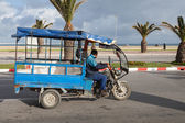 TANGIER, MOROCCO - MARCH 27, 2014: old blue tricycle cargo bike with Arab driver rides on the coastal street of  Tangier. This is traditional small cargo transport for agrarian market trader — Stock Photo