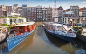 Amsterdam, Holandia - 19 marca 2014: kolorowe łodzie stoją zacumowane na damrak kanał molo w historycznym centrum Amsterdamu — Zdjęcie stockowe