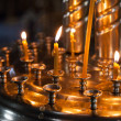 Small candles are lit in a dark Orthodox Church — Stock Photo #44646517