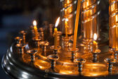 Small candles are lit in a dark Orthodox Church — Stock Photo