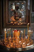 Candles are lit in a dark Orthodox Church above ancient icon — Photo