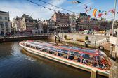 Sightseeing boat goes through the canal in historical central part of Amsterdam — Stock Photo