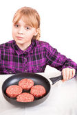 Little blond girl with raw meatballs in the pan on white backgro — Stockfoto