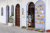 TANGIER, MOROCCO - MARCH 22, 2014: Open door of small souvenir shop with hanging colorful pictures for sale — Stock Photo