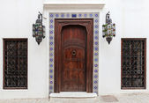 Ancient wooden door and windows on white wall. Tangier, Morocco — Stock Photo
