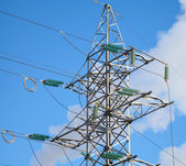 High voltage power lines and large pylon above blue sky — Stock Photo