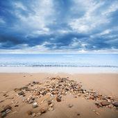 Atlantic ocean coast with wet small stones on the sand — Stock Photo