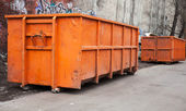 Big metal orange trash containers in the city — Stock Photo