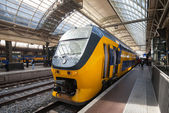 AMSTERDAM, NETHERLANDS - MARCH 19, 2014: Yellow train stands on the central railroad station in Amsterdam — Stock Photo