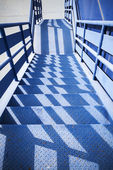 Blue industrial metal staircase perspective with shadows pattern — Stock Photo