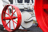 Fragment of old white tractor with red wheels — Stock Photo