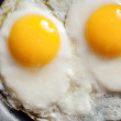 Macro photo of two scrambled eggs in black frying pan — Stock Photo #47211019
