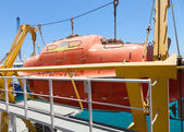 Big red rescue boat hanging on the passenger ship — Stok fotoğraf