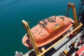 Red rescue boat hanging on the passenger ship — Stok fotoğraf