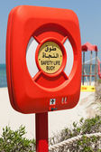 Safety life buoy in red case on the beach in Saudi Arabia — Stok fotoğraf