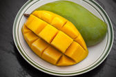 Yellow cubes sliced mango on white plate — Stock Photo