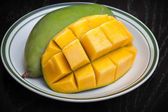 Yellow sliced on cubes mango on white plate — Stock Photo