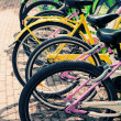 Colorful bicycles stand in row on a parking lot for rent, styliz — Stock Photo #47444793