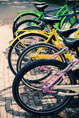 Colorful bicycles stand in row on a parking lot for rent, styliz — Stock Photo