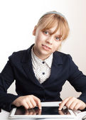 Little blond smiling schoolgirl with tablet device on the desk — Stock Photo