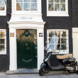 AMSTERDAM, NETHERLANDS - MARCH 19, 2014: Vespa scooter stands parked near old living house in Amsterdam — Stock Photo