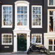 AMSTERDAM, NETHERLANDS - MARCH 19, 2014: black Vespa scooter stands parked near old living house in Amsterdam — Stock Photo #47826571