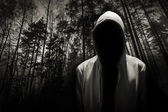 Portrait of dangerous man hiding under the hood in the forest — Stock Photo