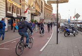 AMSTERDAM, NETHERLANDS - MARCH 19, 2014: ordinary people walking and ride a bicycles on the street — Stock Photo