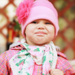 Funny smiling Caucasian baby girl in pink, closeup outdoor portrait — Stock Photo #47959145