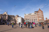 AMSTERDAM, NETHERLANDS - MARCH 19, 2014: Dam Square view with walking tourists and ordinary people — Stock Photo