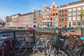 AMSTERDAM, NETHERLANDS - MARCH 19, 2014: Bicycles and colorful houses along canal in spring sunny day — Stock Photo