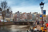 AMSTERDAM, NETHERLANDS - MARCH 19, 2014: Colorful houses and bicycles on the canal coasts in spring day. Ordinary people are walking on the coast — Stock Photo