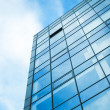 Modern office building wall made of steel and glass with blue sky — Stock Photo #49199779