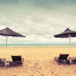 Sunbeds and umbrellas on empty sandy beach. Toned effect — Stock Photo #49199821