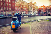 Blue scooter stands parked on the canal coast in Amsterdam — Stockfoto