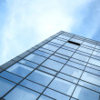 Modern office building wall made of glass and steel with blue sk — Stock Photo #49378177