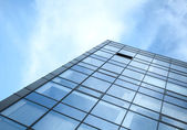 Modern office building wall made of glass and steel with blue sk — Stok fotoğraf