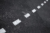 Dark asphalt road background with striped dividing marking line — Stockfoto