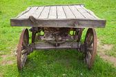 Pusty stary wiejski drewniany wóz stoi na lato zielona trawa — Zdjęcie stockowe