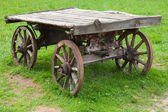 Empty old rural wooden wagon stands on green summer grass — Stock Photo