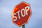 Old stop road sign above blue cloudy sky — Stockfoto